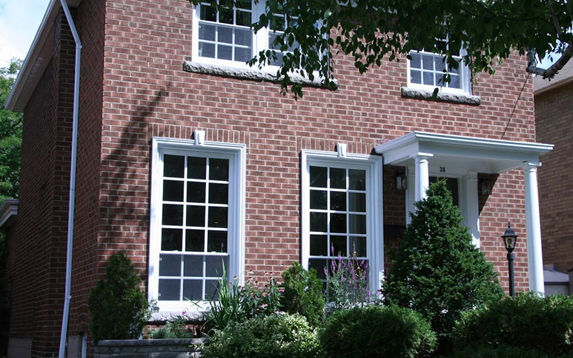 window grilles with white trim on brick home